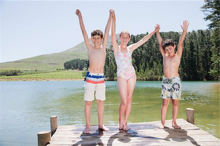 preteen girl wet clothes - Kids standing with arms raised on dock Stock Photo - Premium Royalty-Free, Code: 635-03860202