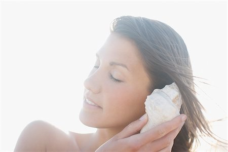 Close up of woman listening to seashell Stock Photo - Premium Royalty-Free, Code: 635-03860285