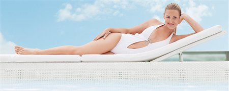 Woman laying on lounge chair at poolside Stock Photo - Premium Royalty-Free, Code: 635-03860349