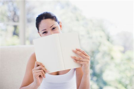 Woman holding book over mouth Stock Photo - Premium Royalty-Free, Code: 635-03860368