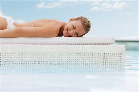 Woman sunbathing at poolside Stock Photo - Premium Royalty-Free, Code: 635-03860404