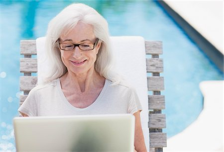 Senior woman using laptop at poolside Stock Photo - Premium Royalty-Free, Code: 635-03860437