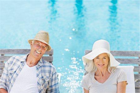 Senior couple wearing sun hats at poolside Stock Photo - Premium Royalty-Free, Code: 635-03860441