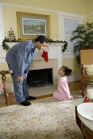 View of brother and sister by fireplace decorated for Christmas waiting for Santa Stock Photo - Premium Royalty-Free, Code: 638-01335097