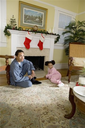 View of brother and sister sitting by fireplace decorated for Christmas, waiting for Santa Stock Photo - Premium Royalty-Free, Code: 638-01331200