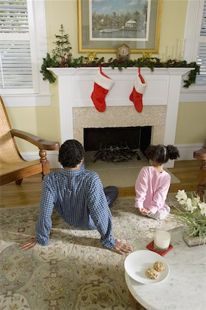 View of brother and sister sitting by fireplace decorated for Christmas, waiting for Santa Stock Photo - Premium Royalty-Free, Code: 638-01331820