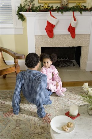 View of brother and sister sitting by fireplace decorated for Christmas, waiting for Santa Stock Photo - Premium Royalty-Free, Code: 638-01331909