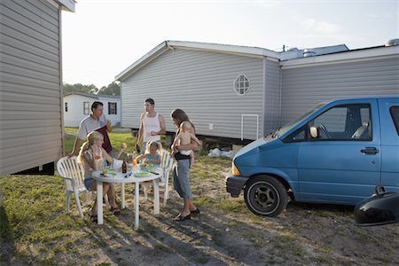 Blue collar families enjoying lunch in front of trailer home Stock Photo - Premium Royalty-Free, Code: 638-01332555