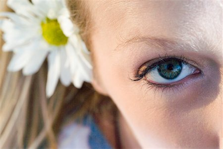 Close-up of a young woman's face, one eye and a flower in her hair visible Stock Photo - Premium Royalty-Free, Code: 638-01583511