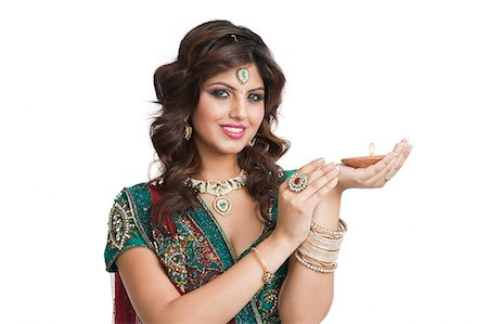 Woman holding an oil lamp on Diwali Stock Photo - Premium Royalty-Free, Code: 630-06724471