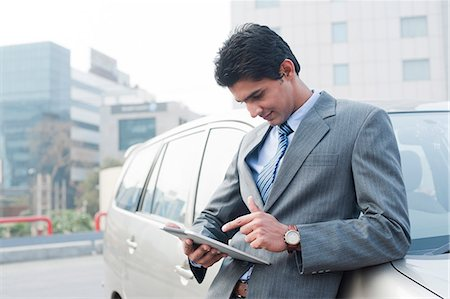 east indian (male) - Businessman standing beside a car and using a digital tablet, Gurgaon, Haryana, India Stock Photo - Premium Royalty-Free, Code: 630-06724618