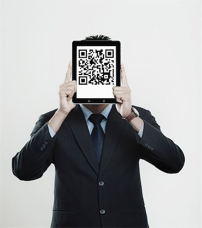 east indian (male) - Businessman holding a digital tablet in front of his face with 2D barcode on it Stock Photo - Premium Royalty-Free, Code: 630-06724610