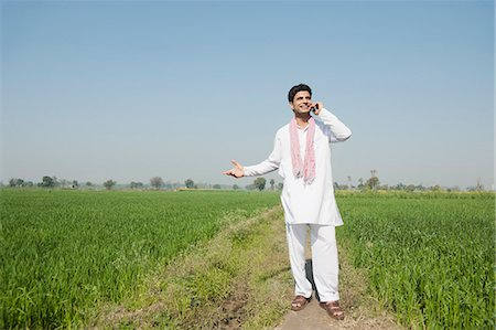 Farmer talking on a mobile phone in the field, Sonipat, Haryana, India Stock Photo - Premium Royalty-Free, Code: 630-06724652