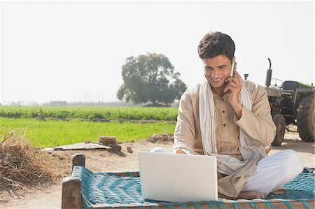 farm phone - Farmer using a laptop and talking on a mobile phone in the field, Sonipat, Haryana, India Stock Photo - Premium Royalty-Free, Code: 630-06724664