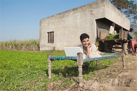 farm phone - Farmer using a laptop and talking on a mobile phone in the field, Sonipat, Haryana, India Stock Photo - Premium Royalty-Free, Code: 630-06724661