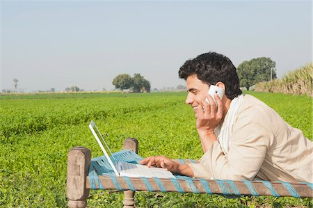 farm phone - Farmer using a laptop and talking on a mobile phone in the field, Sonipat, Haryana, India Stock Photo - Premium Royalty-Free, Code: 630-06724663
