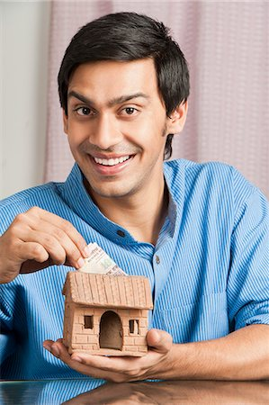 set - Bengali man putting money in a model home Stock Photo - Premium Royalty-Free, Code: 630-06724880