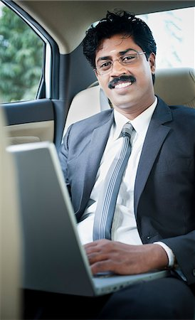 South Indian businessman using a laptop in the car Stock Photo - Premium Royalty-Free, Code: 630-06724905