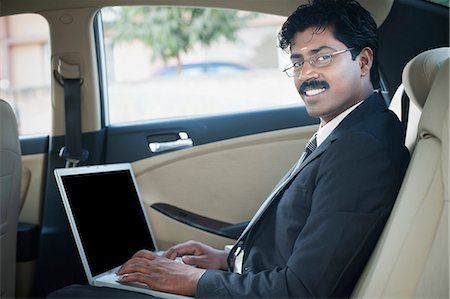 South Indian businessman using a laptop in the car Stock Photo - Premium Royalty-Free, Code: 630-06724906