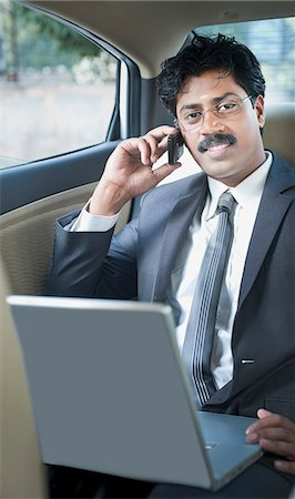 South Indian businessman using a laptop and talking on a mobile phone in the car Stock Photo - Premium Royalty-Free, Code: 630-06724907