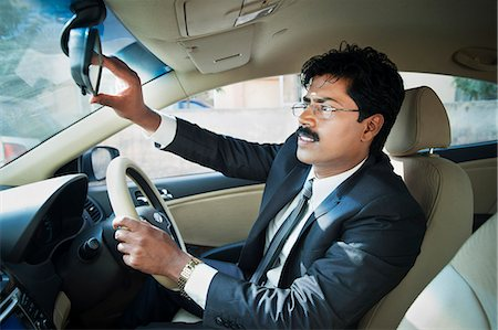 South Indian businessman adjusting the rear view mirror of a car Stock Photo - Premium Royalty-Free, Code: 630-06724908