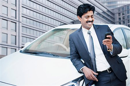 South Indian businessman text messaging on a mobile phone in front of a car Stock Photo - Premium Royalty-Free, Code: 630-06724911