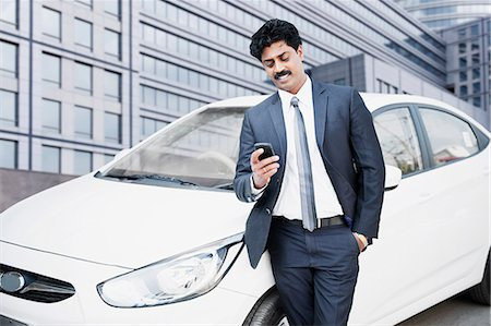 South Indian businessman text messaging on a mobile phone in front of a car Stock Photo - Premium Royalty-Free, Code: 630-06724913