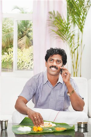 South Indian man having food and talking on a mobile phone Stock Photo - Premium Royalty-Free, Code: 630-06724926