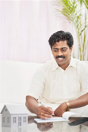 South Indian man signing a check and looking at a model home Stock Photo - Premium Royalty-Free, Code: 630-06724927