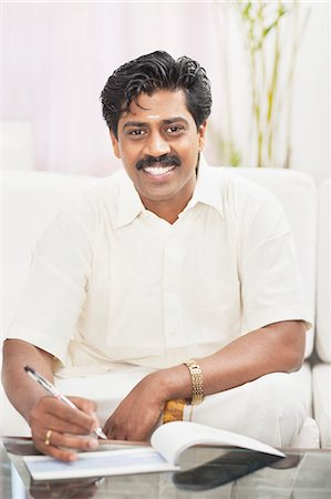 South Indian man signing a check Stock Photo - Premium Royalty-Free, Code: 630-06724928