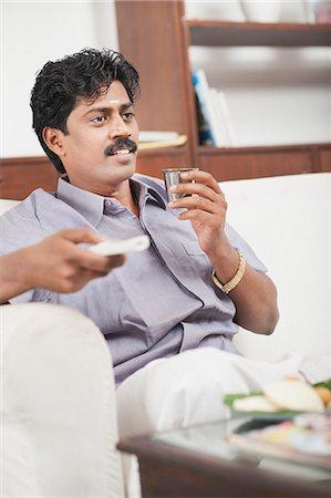South Indian man watching TV and having tea Stock Photo - Premium Royalty-Free, Code: 630-06724920