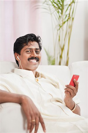 South Indian man listening to a mp3 player Stock Photo - Premium Royalty-Free, Code: 630-06724934