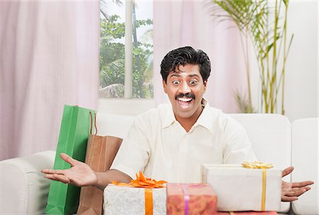 South Indian man smiling near gift boxes Stock Photo - Premium Royalty-Free, Code: 630-06724937