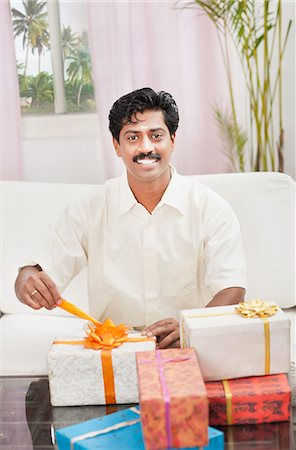 South Indian man smiling near gift boxes Stock Photo - Premium Royalty-Free, Code: 630-06724938