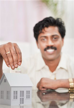 South Indian man putting money in a model home Stock Photo - Premium Royalty-Free, Code: 630-06724930