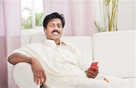 South Indian man listening to a mp3 player Stock Photo - Premium Royalty-Free, Code: 630-06724933