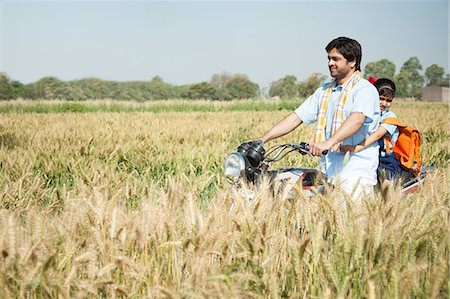 Farmer with his daughter riding a motorcycle in the field, Sohna, Haryana, India Stock Photo - Premium Royalty-Free, Code: 630-06724953