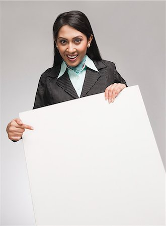 Businesswoman showing a placard and smiling Stock Photo - Premium Royalty-Free, Code: 630-06721998