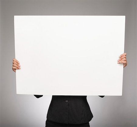 Businesswoman showing a placard Stock Photo - Premium Royalty-Free, Code: 630-06722001