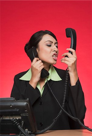 Businesswoman using multiple landline phones and shouting Stock Photo - Premium Royalty-Free, Code: 630-06722040