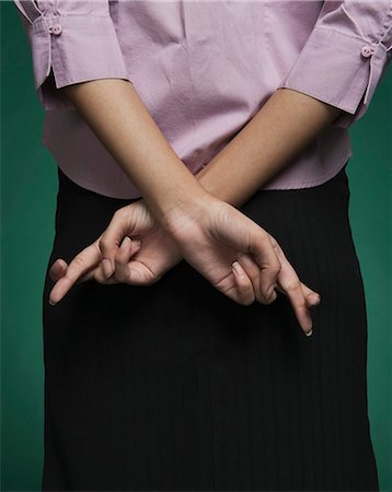 desire - Mid section view of a businesswoman with fingers crossed behind her back Stock Photo - Premium Royalty-Free, Code: 630-06722055