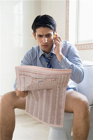 Businessman talking on a mobile phone and reading a newspaper on a toilet seat Stock Photo - Premium Royalty-Free, Code: 630-06722229