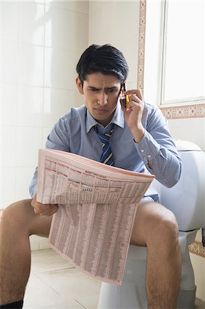 Businessman talking on a mobile phone and reading a newspaper on a toilet seat Stock Photo - Premium Royalty-Free, Code: 630-06722231