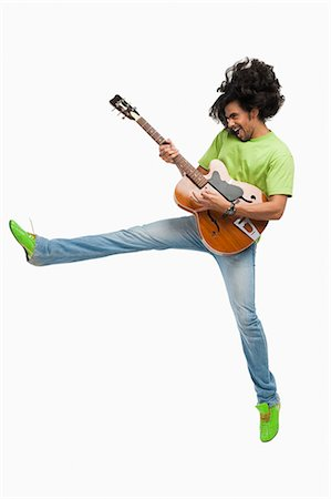 east indian (male) - Man jumping in the air while playing a guitar Stock Photo - Premium Royalty-Free, Code: 630-06722261