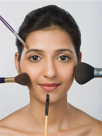 Woman with make-up brushes around her face Stock Photo - Premium Royalty-Free, Code: 630-06722478