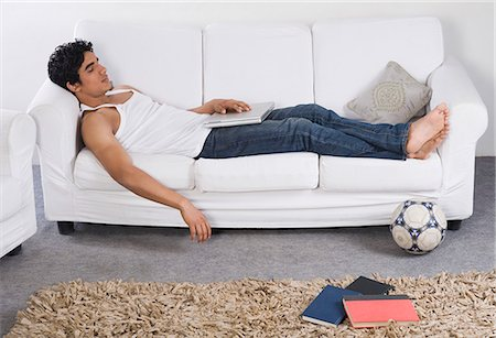 east indian (male) - Man resting on a couch with a laptop Stock Photo - Premium Royalty-Free, Code: 630-06722638