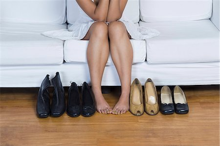 Woman sitting on a couch and choosing footwear Stock Photo - Premium Royalty-Free, Code: 630-06722652