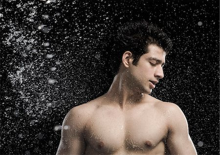 Bare chested man splashed with water Stock Photo - Premium Royalty-Free, Code: 630-06722704
