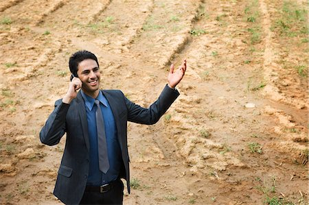 farm phone - Businessman talking on a mobile phone in a field Stock Photo - Premium Royalty-Free, Code: 630-06722927