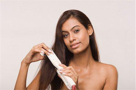 Woman using straightening irons on her hair Stock Photo - Premium Royalty-Free, Code: 630-06722952